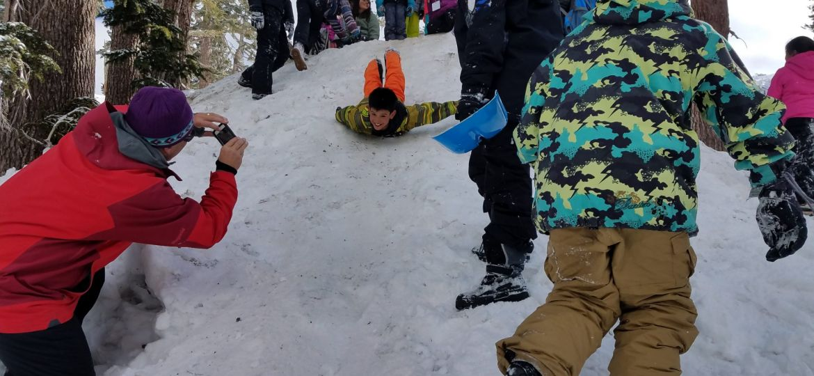 kids sledding at snow school