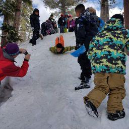 kids sledding at snow school