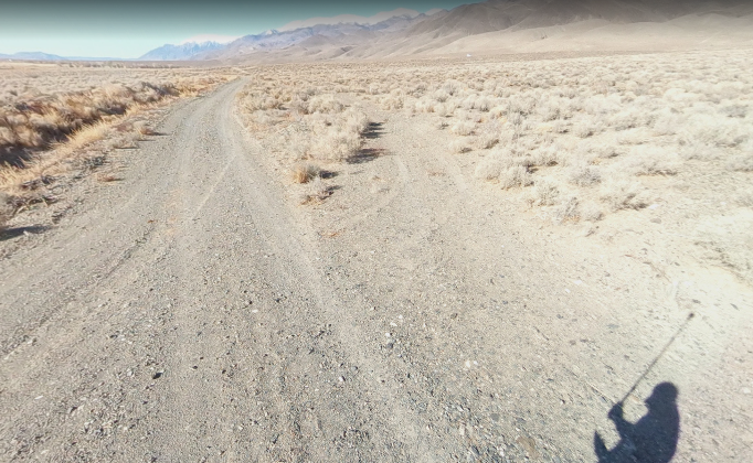 Michael holding 360 degree camera on a dirt road